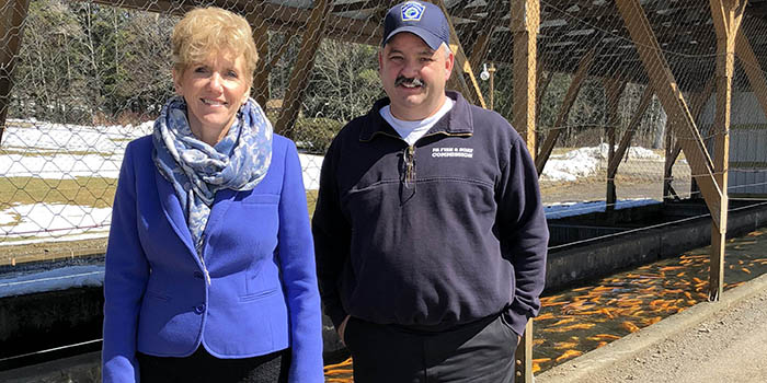 County Executive and hatchery manager stand near trout pools at Corry State Fish Hatchery