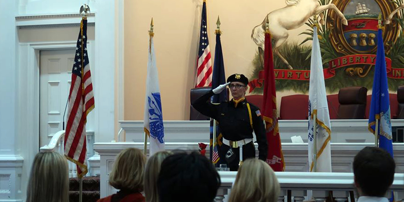 A female veteran salutes during a Veterans Day ceremony