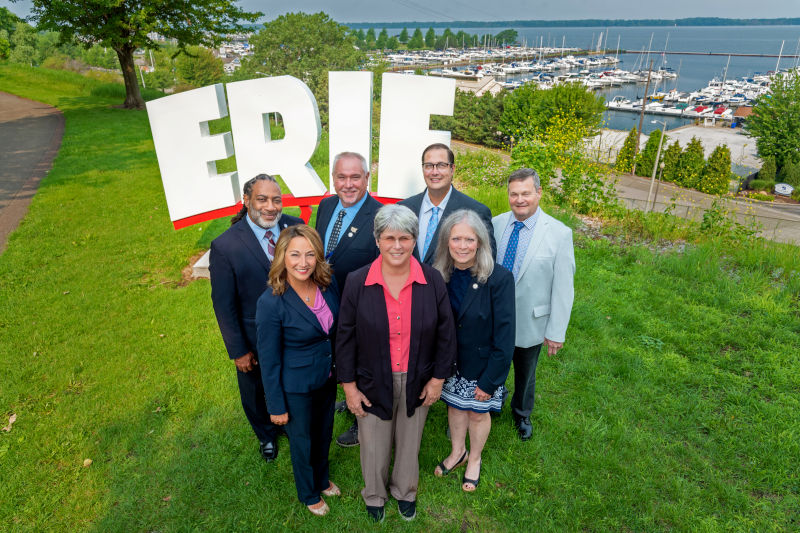 Members of the Erie County Council standing in front of a sign that says ERIE.